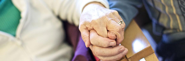 Elderly couple linking hands