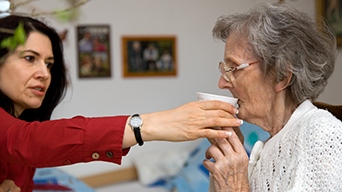 woman giving mother medication
