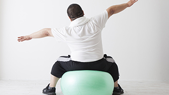 Obese man on exercise ball